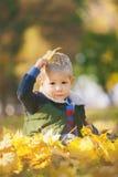 Das nette lustige Kind, das mit Herbstorange spielt, verlässt im Park Stockbild