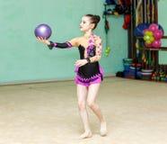 Das nette Mädchen, das geschickten Trick mit Ball auf Kunstgymnastik tut, führen durch stockfotos