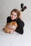Das nette Mädchen mit einer roten Katze auf Händen Lizenzfreie Stockfotografie