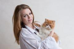 Das nette Mädchen mit einer roten Katze auf Händen Stockfotos