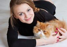 Das nette Mädchen mit einer roten Katze auf Händen Lizenzfreie Stockfotos
