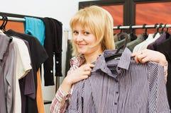 Das nette Mädchen wählt Kleidung in einer Butike Stockbilder
