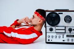 Das nette moderne Manntragen roter Sport entsprechen dem Sitzen mit einem Retro- Tonbandgerät durchdachte Art der neunziger Jahre stockbilder