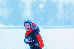 Das nette Spielen des kleinen Jungen äußer und das Werfen weitet im Winter aus Lizenzfreie Stockfotografie
