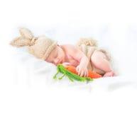 Das nette zwei-Wochen-alte lächelnde neugeborene Baby, das gestricktes Häschenkostüm tragen und die lustige Karotte spielen Lizenzfreies Stockbild