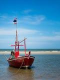Das neue rote Fischerboot machte in dem Meer fest Stockbild