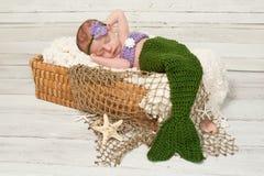 Neugeborenes Baby, das ein Meerjungfrau-Kostüm trägt Stockfotografie