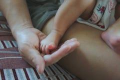 Das neugeborene Baby der Nahaufnahme mit Fuß auf der Hand der Mutter stockfotos