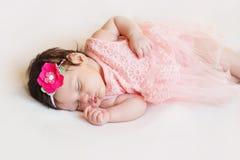 Das neugeborene Mädchenlügen, das auf einer Decke des weißen Haares glücklich und entspannt ist, kleidete im Rosa an lizenzfreie stockfotos