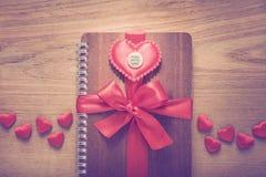 Das Notizbuch, das mit rotem Band eingewickelt wurde, Rot glaubte Herzen mit gemacht mit Lizenzfreie Stockbilder