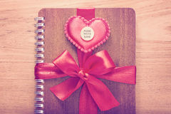 Das Notizbuch, das mit rotem Band eingewickelt wurde, Rot glaubte Herzen mit gemacht mit Lizenzfreies Stockbild