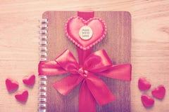 Das Notizbuch, das mit rotem Band eingewickelt wurde, Rot glaubte Herzen mit gemacht mit Stockbild