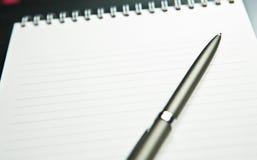 Das Notizbuch mit dem Griff legt auf ein Grau Stockfoto