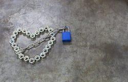 Das Nussherz mit blauem Schlüssel auf dem Metallhintergrund Das Nuss hea Stockbild