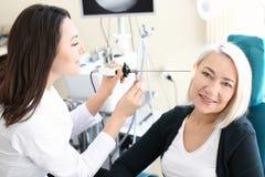 Das Ohr der Untersuchungsfrau des Facharztes für Hals- und Ohrenleiden mit HNOteleskop im Krankenhaus lizenzfreie stockfotografie
