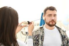 Das Ohr des Untersuchungsmannes des Facharztes für Hals- und Ohrenleiden mit HNOteleskop im Krankenhaus stockfotografie