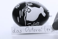 Das Osterei, German word on a white note for English Easter Egg. Learn new language, German word for the English Easter egg written on a note near some chocolate royalty free stock images