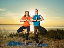 Das Paar, das Yoga macht, trainiert draußen Stockbild