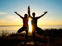 Das Paar, das Yoga macht, trainiert draußen Stockbilder