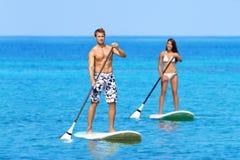 Das Paar-Handeln steht oben Paddleboarding auf Ozean stockfotografie