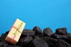 Das Paket mit dem eingewickelten Geschenk liegt auf einem Haufen der schwarzen Kohle stockfoto