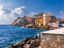 Das perfekte kleine Küstendorf von Giglio Porto mit multi farbigen Häusern lizenzfreies stockbild