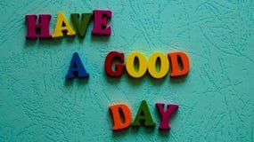 Das Phrase ` haben eine ` des guten Tages hölzerne farbige tadellose Farbe Buchstaben auf dem Tisch Stockbilder