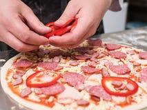 Das Pizzakochen addieren köstliche Mahlzeit des roten Pfeffers Stockfotografie