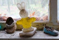 Das Plastikspielzeug und die Schuhe der Kinder auf Fensterbrett in verlassenem Kindergarten in zerstörtem Dorf Kopachi, Tschornob stockfotos