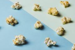 Das Popcorn in der Papierschale auf grünem und blauem Hintergrund stockfotografie