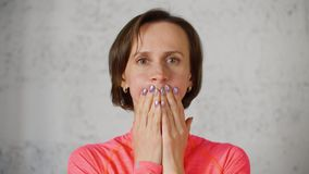 Das Porträt der Frau ihren Mund mit ihren Händen bedeckend stößt oben Backen, Vorderansicht luft stock video