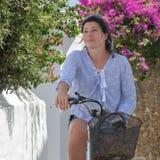 Das Porträt der glücklichen Frau auf einem Fahrrad an den Sommerferien in Andros-Insel in Griechenland lizenzfreie stockbilder