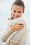 Das Porträt der jungen Frau einwickelnd in der Strickjacke auf kalt setzen auf den Strand Stockfotos
