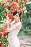 Das Porträt der Nahaufnahme im Freien des lächelnden rührenden Bogens der Braut mit roten Rosen Lizenzfreies Stockbild