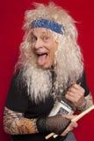 Das Porträt des älteren Musikers Trommelstock halten und der Alkohol füllen beim Zunge heraus haften ab Lizenzfreies Stockbild