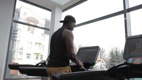 Das Porträt des afroen-amerikanisch Sportlers, der seine exersices auf der Rennstrecke in der modernen Turnhalle beendet stock footage