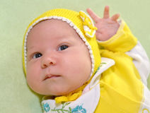 Das Porträt des Babys in einer gelben Kappe auf einem grünen Hintergrund Stockbilder