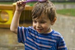 Das Porträt des glücklichen Jungen unter strömendem Wasser Lizenzfreie Stockfotos