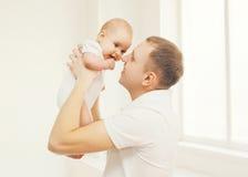 Das Porträt des glücklichen Vaters an halten übergibt sein Baby Lizenzfreie Stockfotos