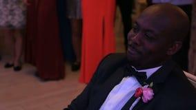 Das Porträt des hübschen afrikanischen Bräutigams in der stilvollen Klage, die mit Boutonniere verziert wird, schaut weg während  stock video footage