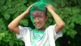 Das Porträt des Jungen sein Haar und heiliges Pulver durcheinander bringend fällt aus seinem Haar heraus stock video footage