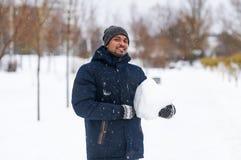 Das Porträt des Kerls hält Schnee in der Hand Stockfotos