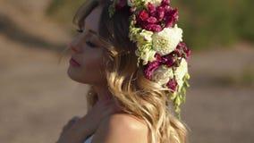 Das Porträt des schönen Mädchens mit dem BlumeKranz und im weißen Kleid während ihrer Feiertage in den Bergen stock footage