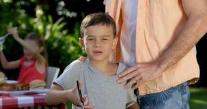 Das Porträt des Vaters ein Auge auf seinem Sohn halten bereitet einen Grill vor stock footage