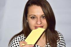 Das Porträt einer beißenden Schokolade der jungen Frau des Brunette lizenzfreie stockfotos