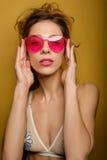 Das Porträt eines jungen Mädchens in einem Badeanzug mit dem erfassten Haar, die Finger des Bogens der rosa Gläser halten und bet Lizenzfreie Stockfotografie