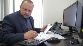 Das Porträt von männlichem finanziellanalytischem, wer an seinem Bericht in seinem Privatbüro arbeitet stock video footage