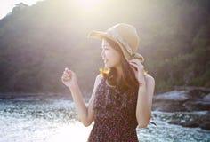 Das Porträt der jungen Schönheit langes Kleid tragend und der breite Strohhut, der am Seeseiten-Standortgebrauch für modernes Leb Stockfoto