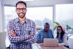 Das Porträt des glücklichen Geschäftsmannes stehend mit den Armen kreuzte im Büro Lizenzfreies Stockbild