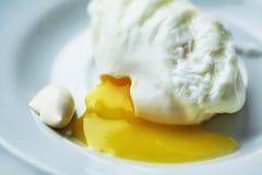 Das poschierte Ei ist auf einer weißen Platte Stockfoto